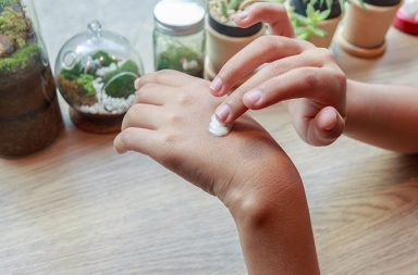 A woman applying a topical pain relief product that includes CBD