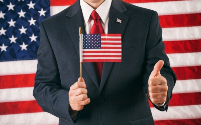politician holding mini american flag against american flag backdrop