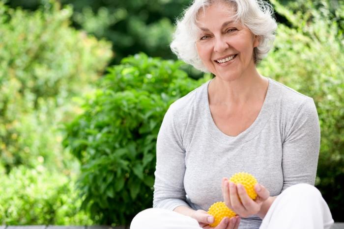 elderly woman wearing grey sweatshirt holding lemons