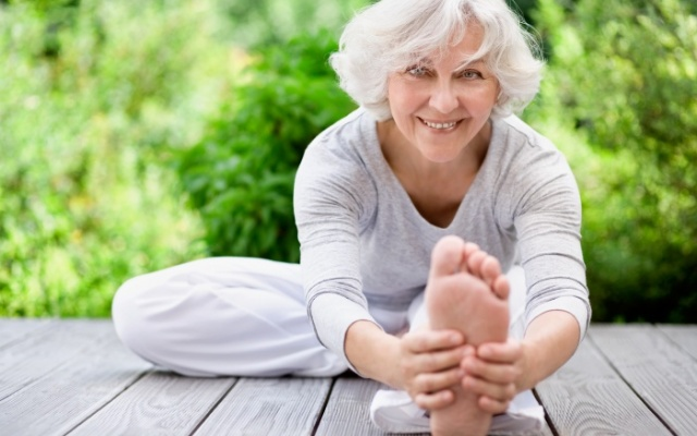 elderly woman stretching outside on a wooden deck