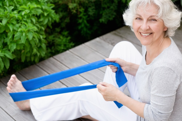 senior woman stretching her legs outside on a wooden deck with resistance band