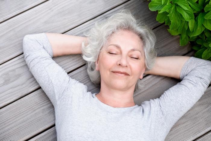 elderly woman laying downoutside on wooden deck relaxing