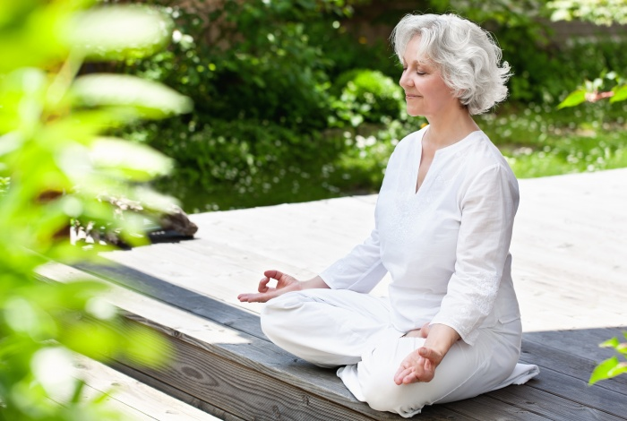 senior woman meditating practicing good self care outside on a wooden deck