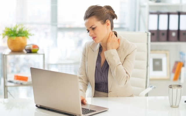 Business woman at desk with neck pain
