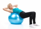 Aged Lady Lying On Fitness Ball. Blond Woman Workout On White Background