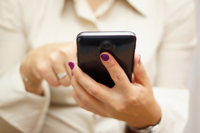 woman with purple nail polish on cell phone