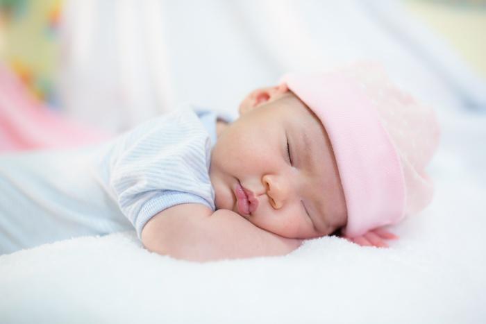 newborn baby resting wearing pink hat
