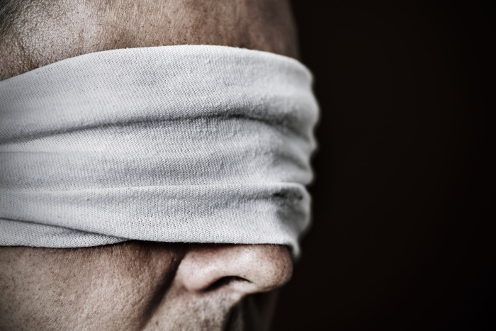 closeup of a young man with a blindfold in his eyes, as a symbol of oppression or repression