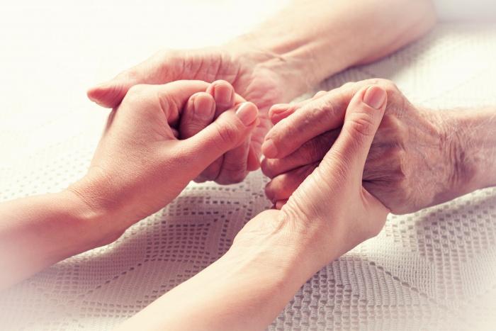 elderly person having both hands held