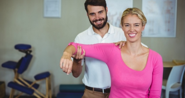 Male physiotherapist giving arm massage to female patient