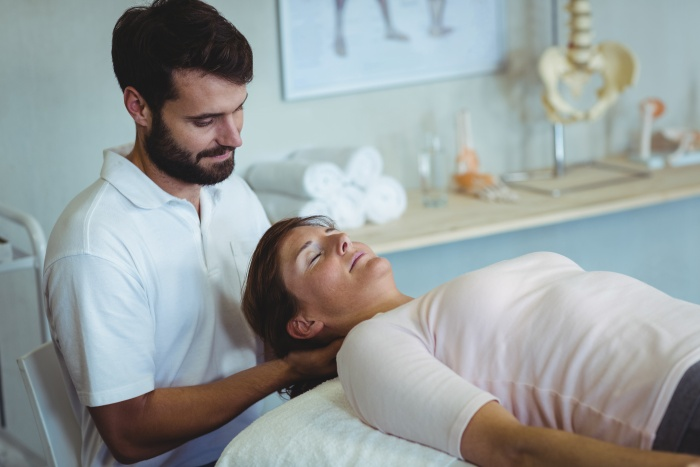 Physiotherapist giving neck massage to a woman