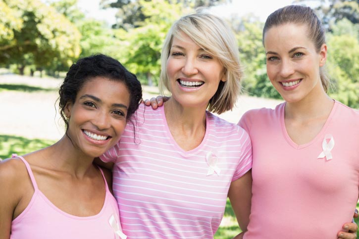 Women smiling with breast cancer awareness ribbons