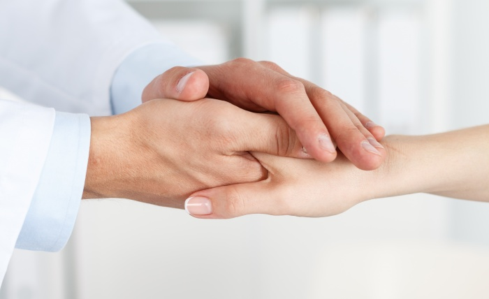 doctor holding patient's hand showing compassion and empathy