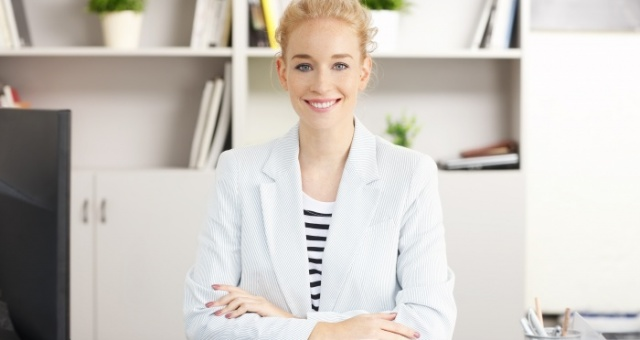 Portrait of young health coach sitting at office with arms crossed in front of computer while looking at camera and smiling.
