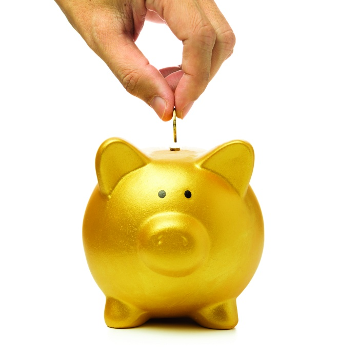 Close up of hand putting coin into golden piggy bank for tax tips