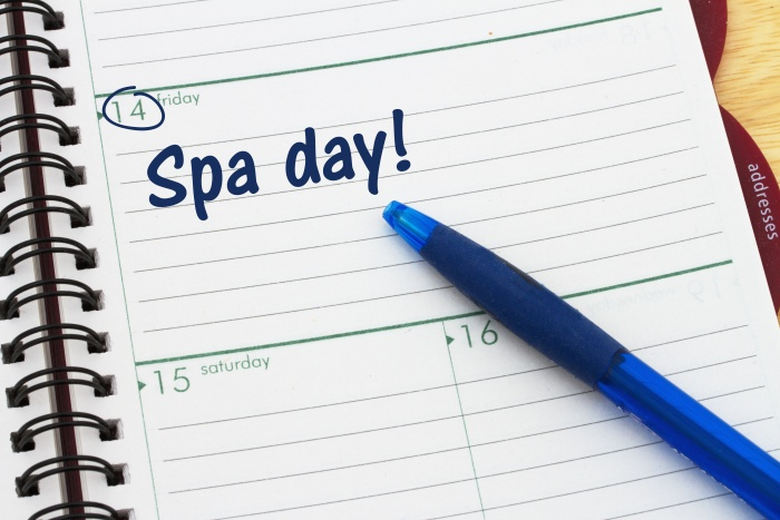 Scheduling your spa day's appointment , A day planner with blue pen with text Spa Day