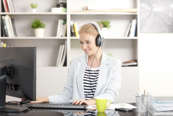 Portrait of smiling health coach using headphone and listening music while typing at keyboard in her workplace.